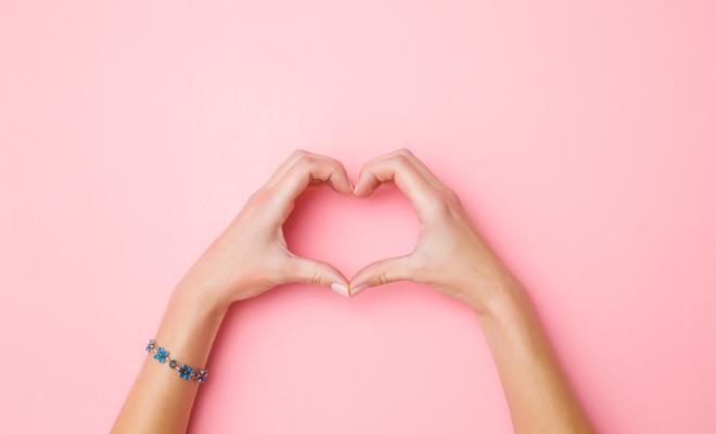 corazon con manos en fondo rosa